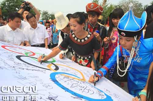 奥运会闭幕式民族国歌合唱团的成员们在奥林匹克会旗上签下自己的名字和寄语