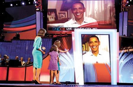 没有到场的奥巴马通过大屏幕向妻子女儿问好