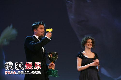 主持人送花给皮特,皮特手拿奖杯鲜花好不得意