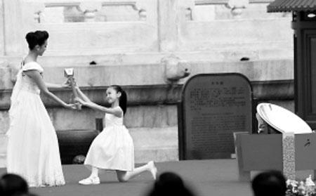残奥会圣火采集使者姜馨田走向采火区,从10岁聋女汪伊美的手中接过引火棒。晨报记者 蔡代征/摄