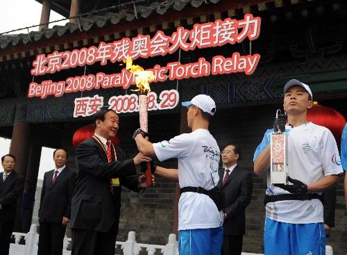 8月29日,北京奥组委执行副主席蒋效愚(前左)接过火炬。当日,北京残奥会圣火在西安进行传递。新华社记者金良快摄