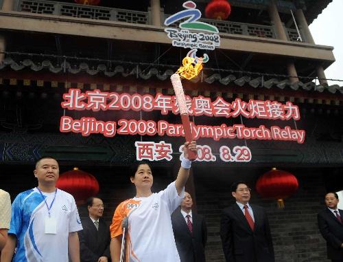 8月29日,第一棒火炬手张辉展示火炬。新华社记者金良快摄