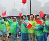 图文:残奥会圣火在西安传递 市民冒雨加油