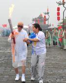 图文:火炬手董应龙在工作人员搀扶下传递火炬