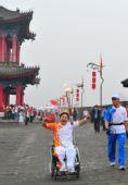 图文:残奥会圣火在西安进行传递 火炬手吴亚明