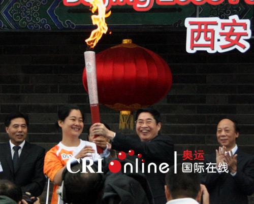 陕西省省长袁纯清将火炬交给第一棒火炬手张辉