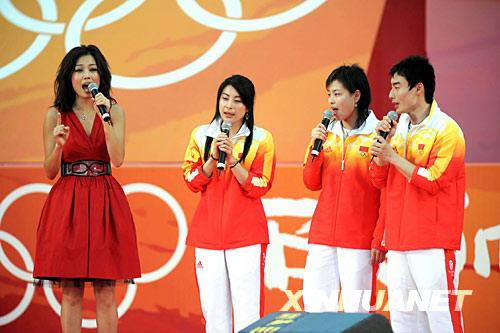 """8月30日,奥运跳水金牌运动员郭晶晶(左二)、吴敏霞(右二)、林跃(右一)与香港艺人容祖儿一起唱歌。当日,""""奥运金牌精英大汇演""""在香港大球场举行。 新华社记者卢炳辉摄"""