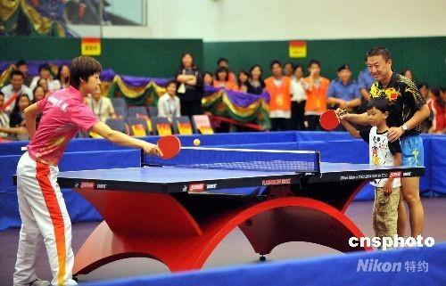男单金牌得主马琳指导一位小朋友与女单金牌得主张怡宁砌磋球技。 中新社发 邓庆乐 摄