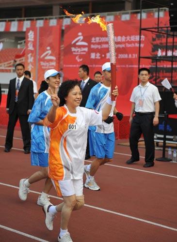 第一棒火炬手程瑜手持火炬传递。当日,北京残奥会圣火在武汉进行传递。 新华社记者郝同前摄