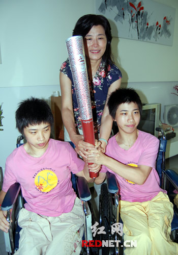 任菲莉和两位脑瘫的孩子和火炬合个影。来源:红网