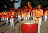 图文:残奥会圣火南京传递 市民在路线旁表演