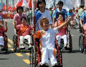 图文:北京残奥会圣火在青岛传递 火炬手李淑兰