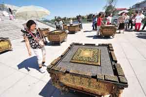"""一名游客正在观看北京奥运会开幕式上使用过的""""缶""""道具"""