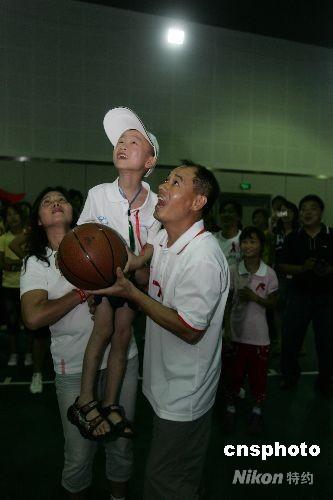 """8月14日下午,李宁、杨扬和潘晓婷在李宁公司与艾滋孤儿玩起了羽毛球、乒乓球等体育游戏。""""快乐奥运会""""由李宁基金会发起,与阜阳市艾滋病贫困儿童救助协会联手,邀请阜阳的30名艾滋孤儿来到北京,观看了奥运会的射击比赛,并游览北京名胜古迹。图为李宁(右)在教艾滋孤儿打篮球。中新社发沈晨 摄"""