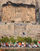 图文:火炬手在洛阳龙门石窟前展示圣火