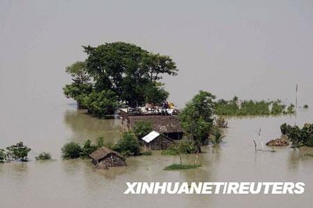 9月3日,在印度东部比哈尔邦一个村庄,一名商贩在被洪水包围的货摊旁等待生意。比哈尔邦连日暴雨导致戈希河河堤决口。目前,比哈尔已有300万人被迫离开家园,另有至少90人在洪水中丧生。 新华社/路透