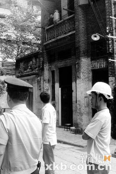 一名男子(圈中所示)抱出煤气罐声称要与房子共存亡。新快报记者 林菁/摄