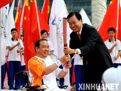 9月3日,大连市市长夏德仁(右)将火炬交给第一棒火炬手李扬。当日,北京残奥会圣火在大连进行传递。 新华社记者李钢摄