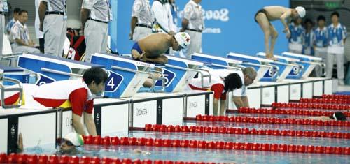 参加男子100米自由泳-S3预赛第二组的选手在工作人员帮助下入水