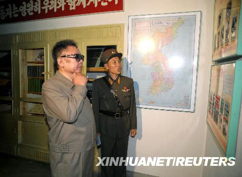 朝鲜中央通讯社8月5日发布的照片显示,朝鲜领导人金正日(前)在视察军队时听取讲解员的讲解。