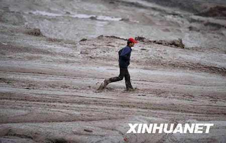 9月8日,一位村民走在泥石流中。 新华社记者 江宏景 摄