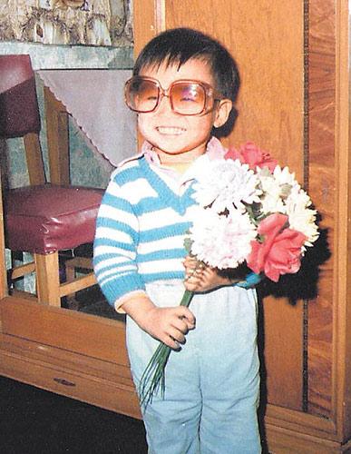 3岁的他戴上太阳眼镜、拿着假花,很像小童星。
