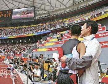 苏桦伟(左)在100米赛事中夺得铜牌,在终点附近守候他冲线的刘德华,上前拥抱对方安慰及鼓励。(图片来源:明报)