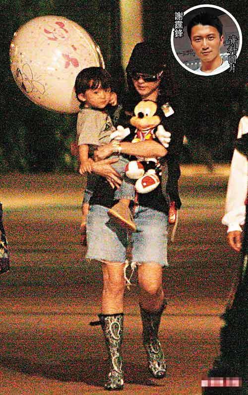 张柏芝抱儿子和米奇老鼠毛公仔夜游士尼乐园,拎气球的小Lucas13个月大,头发浓密,非常精灵可爱。