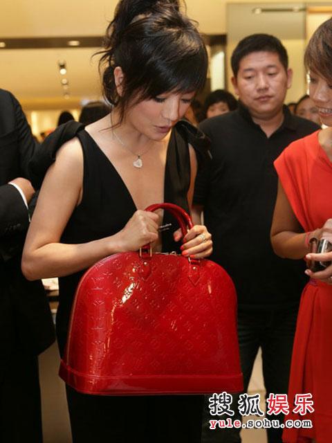 赵薇拿起一个红色新款包,比比是否与身上的衣服搭调