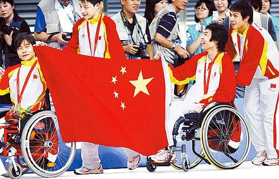 9月15日,中国队队员举起国旗庆祝夺冠。中国队在北京2008年残奥会男子4X50米混合泳接力决赛中,以2分33秒15的成绩打破世界纪录并获得冠军。 新华社记者 丁旭摄