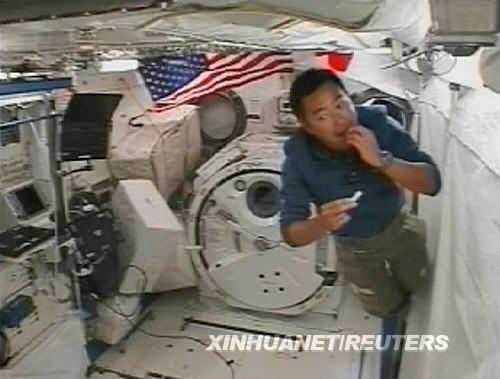 """日本宇航员星出彰彦在国际空间站上的""""希望""""号实验舱内吃零食(美国宇航局6月7日电视画面)。新华社/路透"""