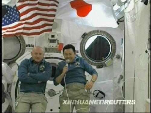 """""""发现""""号机组指令长马克·凯利(左)和日本宇航员星出彰彦在国际空间站上的""""希望""""号实验舱内回答日本官员的提问(美国宇航局6月7日电视画面)。新华社/路透"""