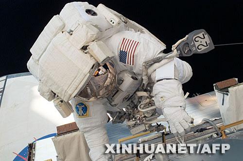 """这张由美国宇航局6月4日提供的照片显示的是,6月3日,美国""""发现""""号航天飞机宇航员罗纳德·加朗在国际空间站上出舱太空行走。新华社/法新"""
