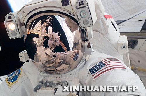 """这张由美国宇航局6月4日提供的照片显示的是,6月3日,美国""""发现""""号航天飞机宇航员罗纳德·加朗(面罩上的反射身影)在国际空间站出舱太空行走过程中为队友迈克尔·福萨姆拍照。新华社/法新"""