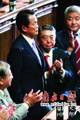 麻生太郎(左二)在当选首相后起立接受议员的祝贺。新华社发