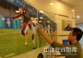 图文:秦皇岛举办奥运足球图片展 细心张贴