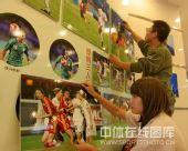 图文:秦皇岛举办奥运足球图片展 认真工作