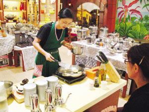 销售员正在为顾客演示高档炊具的烹饪功能