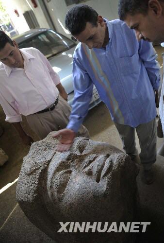 9月28日,埃及东部省文物部主任易卜拉欣(中)和塔拉巴斯塔古迹发掘部主任纳斯夫在埃及塔拉巴斯塔介绍新发现的古埃及法老拉美西斯二世巨石头像。