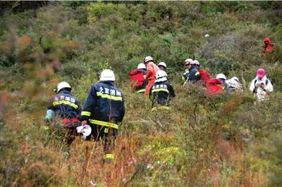消防队员正在大山中进行搜救。 本报实习生王苡萱摄