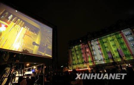 10月4日晚,在法国巴黎火车东站,艺术家们在一块透明的玻璃板上现场作画,并将图画投映在车站对面大楼的墙壁上。新华社记者张玉薇摄