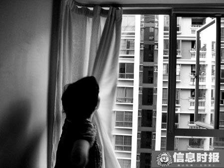 代孕者拉开她所租住房间的窗帘以示居住环境优良。专题摄影 时报记者