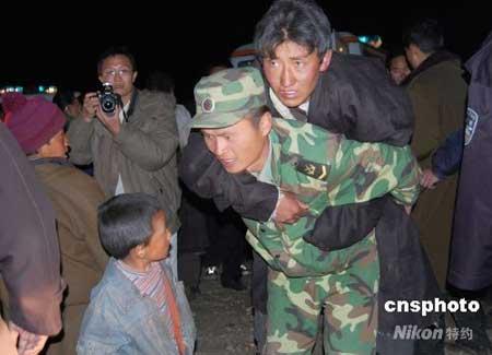 10月6日16时30分拉萨市当雄县境内生6.6级地震,由西藏自治区、拉萨市各职能部门、解放军、武警官兵、医务工作者以及来自四面八方的志愿者组成的救援队,在第一时间赶到位于地震中心位置的当雄县格达乡,他们趁着夜色,在海拔4000多米的高寒地带进行生命救援。图为6日当夜,救援者们在营救灾民。中新社发周波 摄