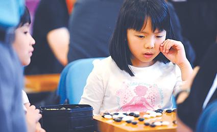 8岁的中国香港小棋手岑乐施在智运会赛场显得格外引人注目