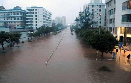 内涝严重 防洪形势严峻 10月14日,海口街道成河道。 10月11日以来,海南省持续的暴雨强风造成全省9个市县157个村庄被淹,近5万群众被迫转移。海口市区龙华路、龙昆南路、红城湖路等多条主要路段内涝严重,大面积交通瘫痪,不少居民家中被淹,出行及日常生活出现困难。 新华社记者 邓伽 摄