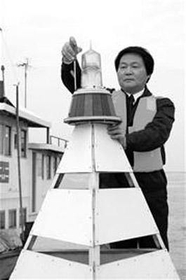 图为:郑启湘和他的太阳能一体化航标灯
