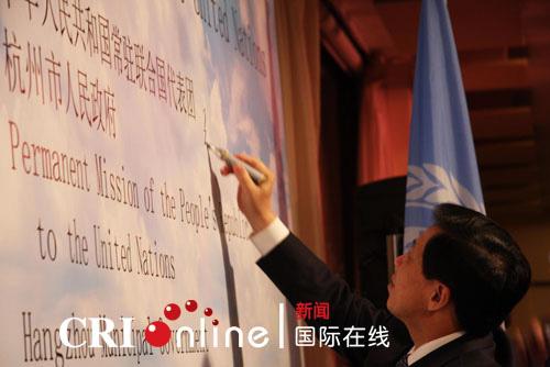 中国常驻联合国代表张业遂在活动展板上签名留念