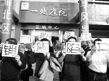 业主们举牌抗议 商报记者 陈亮/摄