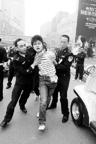 涉嫌妨碍执行公务,男子被警方带走 商报记者 邓万里/摄