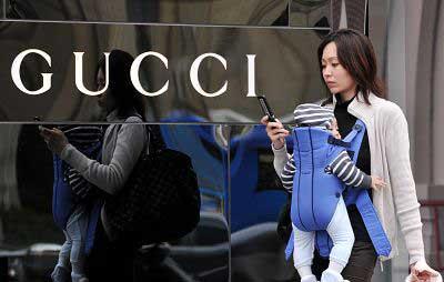 一位时尚妈妈背着宝宝走过名牌专卖店。曹磊 早报资料